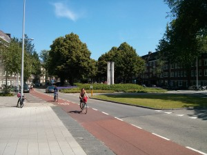 Churchill Laan in Amsterdam has two roads - one for each direction separated by a large green area, each road has a cycle path and there are six lines of trees along the road.